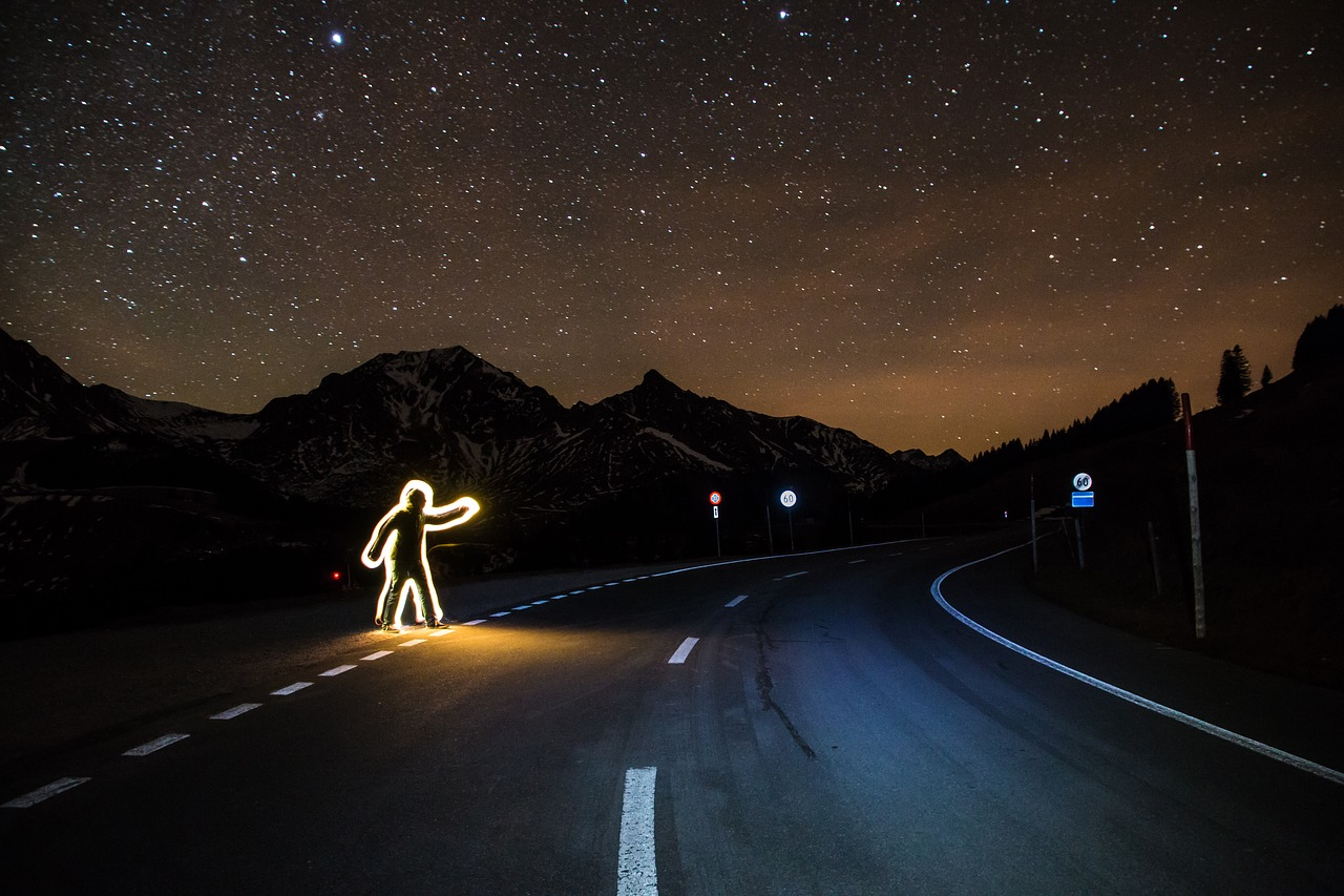 homme illuminé faisant du stop de nuit, photo d'illustration